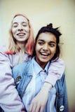 Dos adolescentes delante del edificio de la universidad que sonríen, teniendo Fotos de archivo libres de regalías