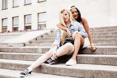 Dos adolescentes delante del edificio de la universidad que sonríen, teniendo Fotos de archivo