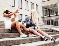 Dos adolescentes delante del edificio de la universidad que sonríen, teniendo Foto de archivo libre de regalías