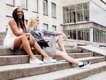 Dos adolescentes delante del edificio de la universidad que sonríen, teniendo Imágenes de archivo libres de regalías