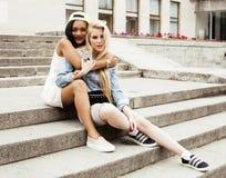 Dos adolescentes delante del edificio de la universidad que sonríen, teniendo Foto de archivo
