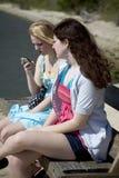 Dos adolescentes en banco con el teléfono celular Foto de archivo libre de regalías