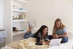 Dos adolescentes en cama usando el ordenador portátil Foto de archivo
