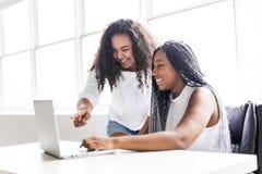 Dos adolescentes en el escritorio en su oficina con el ordenador portátil Imagen de archivo libre de regalías