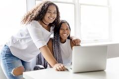 Dos adolescentes en el escritorio en su oficina con el ordenador portátil Imagen de archivo