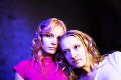 Dos adolescentes en el fondo azul que mira para arriba Foto de archivo libre de regalías