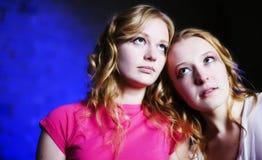 Dos adolescentes en el fondo azul que mira para arriba Fotografía de archivo