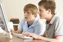 Dos adolescentes en el ordenador en el país Imagenes de archivo