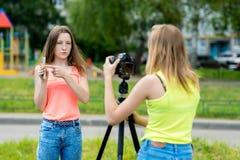 Dos adolescentes En el verano en la ciudad Escribe el vídeo a la cámara Conceptos de bloggers jovenes y de bloggers Foto de archivo libre de regalías