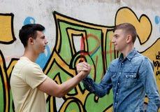Dos adolescentes en la calle que se saludan Foto de archivo