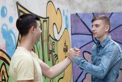 Dos adolescentes en la calle que se saludan Fotografía de archivo