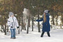 Dos adolescentes en la ropa caliente que juega bolas de nieve entre los árboles en el invierno Fotografía de archivo libre de regalías