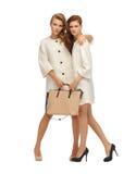 Dos adolescentes en las capas blancas con el bolso Foto de archivo libre de regalías