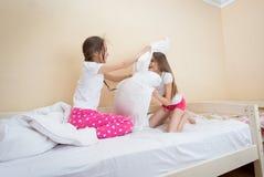 Dos adolescentes en los pijamas que se divierten y que luchan con la almohada Imagen de archivo libre de regalías