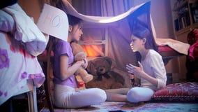 Dos adolescentes en los pijamas que se sientan con la linterna en tienda de la tienda de los indios norteamericanos en dormitorio Foto de archivo