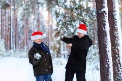 Dos adolescentes en los sombreros Santa Claus de la Navidad que se divierte en el sn Imagen de archivo