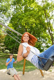Dos adolescentes en patio del oscilación en parque Foto de archivo