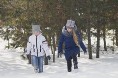 Dos adolescentes en ropa caliente que caminan a través de la nieve entre los árboles en el invierno Foto de archivo