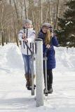 Dos adolescentes en ropa caliente que caminan y que juegan afuera en el invierno Fotografía de archivo libre de regalías
