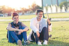 Dos adolescentes en un buen humor con un monopatín Fotos de archivo libres de regalías