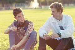 Dos adolescentes en un buen humor con un monopatín Fotos de archivo