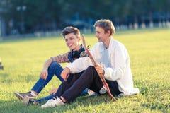Dos adolescentes en un buen humor con un monopatín Imagenes de archivo