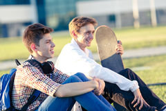 Dos adolescentes en un buen humor con un monopatín Imagen de archivo libre de regalías