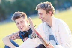 Dos adolescentes en un buen humor con un monopatín Imagen de archivo