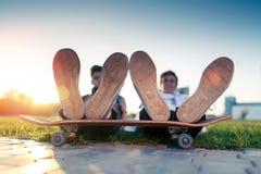 Dos adolescentes en un buen humor con un monopatín Foto de archivo libre de regalías