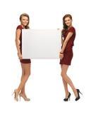 Dos adolescentes en vestidos rojos con el tablero en blanco Imagenes de archivo