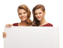 Dos adolescentes en vestidos rojos con el tablero en blanco Imagen de archivo