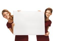 Dos adolescentes en vestidos rojos con el tablero en blanco Foto de archivo libre de regalías