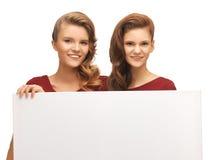 Dos adolescentes en vestidos rojos con el tablero en blanco Fotografía de archivo