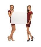 Dos adolescentes en vestidos rojos con el tablero en blanco Imágenes de archivo libres de regalías
