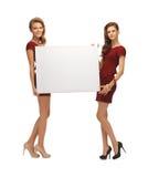 Dos adolescentes en vestidos rojos con el tablero en blanco Fotos de archivo