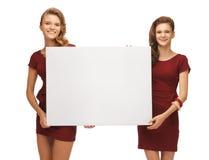 Dos adolescentes en vestidos rojos con el tablero en blanco Foto de archivo