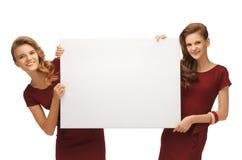 Dos adolescentes en vestidos rojos con el tablero en blanco Fotos de archivo libres de regalías