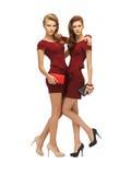 Dos adolescentes en vestidos rojos con los embragues Imagen de archivo