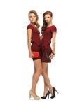 Dos adolescentes en vestidos rojos con los embragues Imagenes de archivo