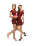 Dos adolescentes en vestidos rojos con los embragues Foto de archivo libre de regalías