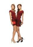 Dos adolescentes en vestidos rojos con los embragues Imágenes de archivo libres de regalías