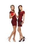 Dos adolescentes en vestidos rojos con los embragues Fotografía de archivo libre de regalías