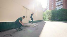 Dos adolescentes están patinando al aire libre en día de verano soleado La gente urbana joven está saltando sobre el pórtico con  almacen de video
