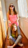 Dos adolescentes felices divertidos que tienen montar a caballo de la diversión Imagen de archivo libre de regalías