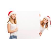 Dos adolescentes felices en los sombreros de la Navidad que sostienen una bandera Imagen de archivo libre de regalías
