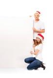 Dos adolescentes felices en los sombreros de la Navidad que sostienen una bandera Imagenes de archivo