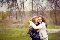 Dos adolescentes felices que abrazan en el parque adentro Imágenes de archivo libres de regalías