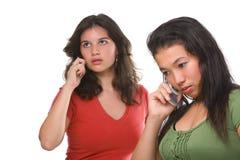 Dos adolescentes femeninos en el teléfono Imágenes de archivo libres de regalías