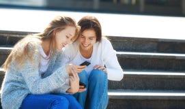 Dos adolescentes femeninos felices que hablan junto en la calle Imágenes de archivo libres de regalías
