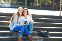 Dos adolescentes femeninos felices que hablan junto en la calle Fotografía de archivo libre de regalías